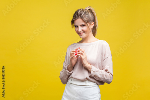 Portrait of smart cunning young woman with fair hair in casual beige blouse standing with sly expression, scheming planning devious tricks, cheating Canvas Print