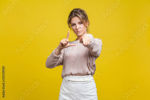 фотографія You are loser! Portrait of serious bossy woman with fair hair in casual blouse standing, showing loser gesture and pointing at camera with angry look