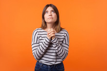 Portrait Of Faithful Young Woman With Brown Hair In Long Sleeve Shirt Standing, Looking Up And Holding Hands In Prayer, Pleading Help Or Apology. Indoor Studio Shot Isolated On Orange Background