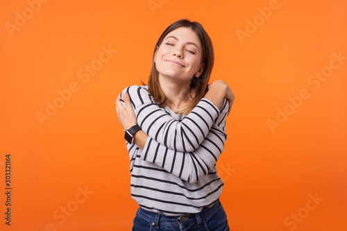 Fotomural I love myself! Portrait of gentle lovely beautiful woman with brown hair in long sleeve shirt standing with closed eyes hugging herself, being selfish