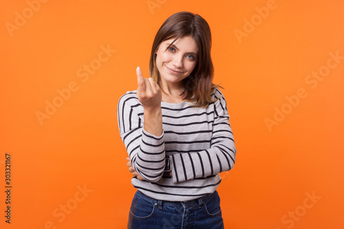 Portrait of friendly pretty young woman with brown hair in long sleeve striped shirt standing, beckoning with finger to come nearer, smiling at camera Wallpaper Mural