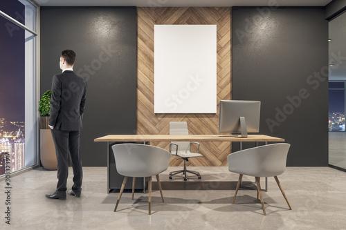 Fototapeta Businessman in modern office interior with billboard obraz na płótnie