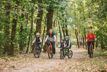 Parents And Kids Cycling On Fo...
