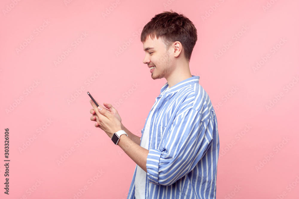 Fototapeta Side view of happy young brown-haired man with small beard in casual striped shirt holding phone, smiling while browsing social media, reading message. indoor studio shot isolated on pink background