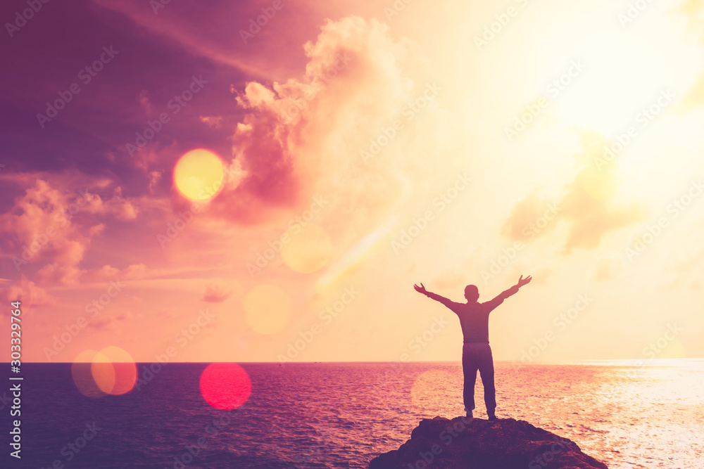 Fototapeta Copy space of happy man hand raise on top mountain at tropical beach and sunset sky abstract background.