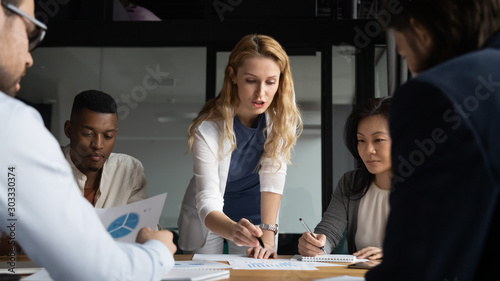 Young businesswoman explaining research results in graphs to colleagues Fototapeta