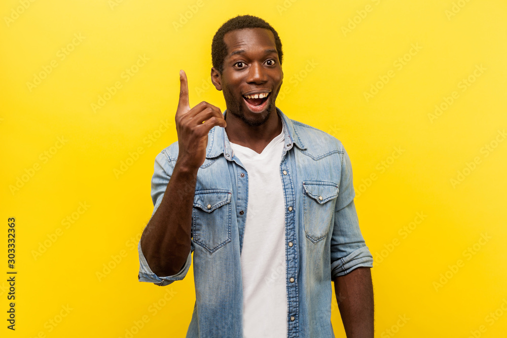 Fototapeta Portrait of creative inspired man in denim casual shirt pointing finger up, showing great idea sign, looking surprised by sudden solution, genius thoughts. studio shot isolated on yellow background
