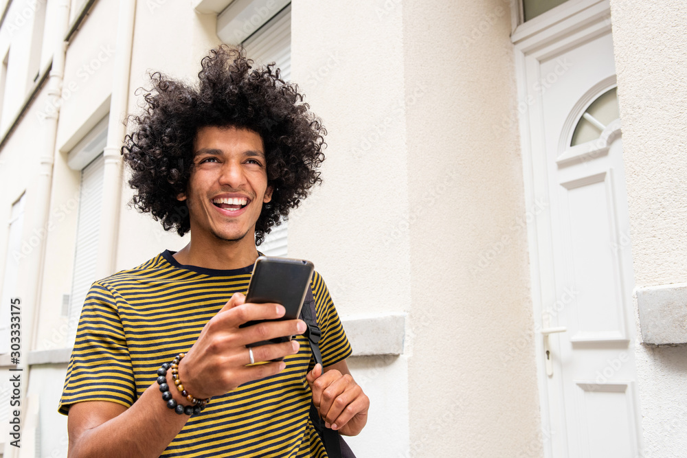 Fototapeta Close up happy young man holding mobile phone