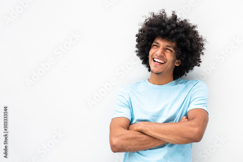 Photo smiling young man with afro hair and arms crossed smiling by white background