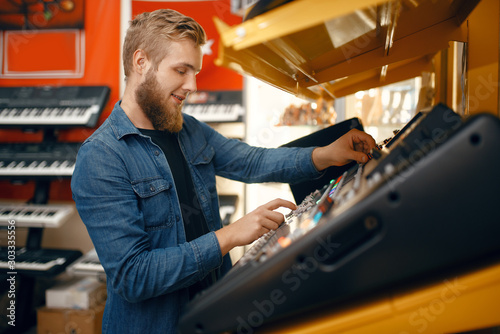 Autocollant pour porte Magasin de musique Young man choosing synthesizer in music store