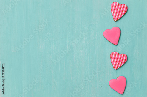 Cookies covered with pink icing on a turquoise background Canvas Print