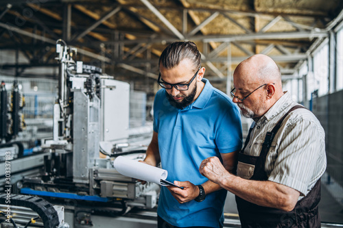 Obraz Two people work at plant on special machine, focused on work - fototapety do salonu