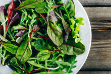 Mix Of Fresh Green Salad Leaves With Arugula, Lettuce, Spinach And Beets On Wooden Rustic Background.