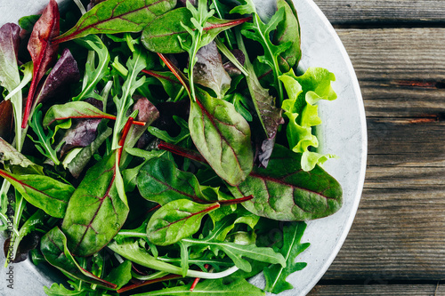 Fotografía  Mix of fresh green salad leaves with arugula, lettuce, spinach and beets on wooden rustic background