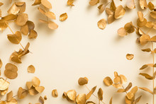 Flat Lay Of Gold Leaves Eucalyptus Populus On Beige Yellow Background. Top View Layout
