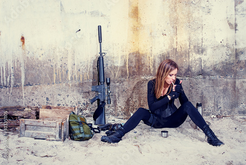 A badass lady in a black catsuit smokes a cigarette while sitting near her combat equipment Canvas Print
