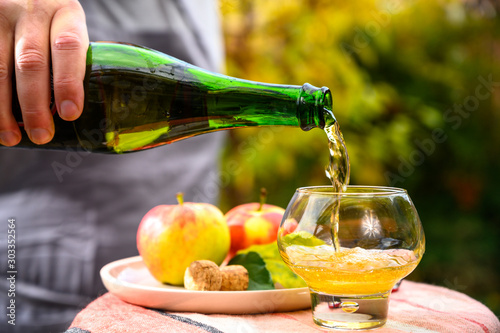 Fotografiet Tasting of french apple cider made from new harvest apples outdoor in orchard