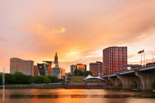 Obraz The skyline of Hartford, Connecticut at sunset. Photo shows Founders Bridge and Connecticut River. Hartford is the capital of Connecticut.  - fototapety do salonu