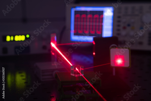 Obraz Experiment in optic lab with laser device. Red laser on optical table in physics laboratory - fototapety do salonu
