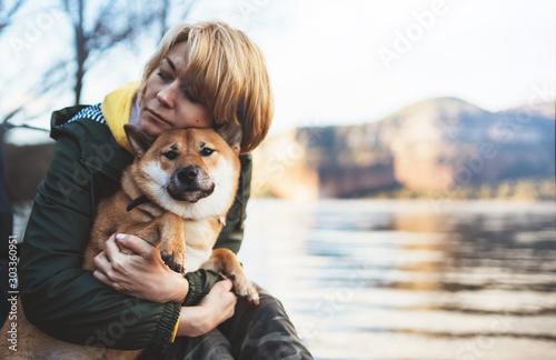 Fototapeta tourist traveler girl together dog background mountain lake, happy woman hug puppy pet nature, friendship love concept obraz