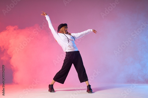 Young cheerful girl with long red hair, wearing black pants, white sportive sweater and stylish hat, dancing energetic funk dance, isolated in colourful smoke background - 303362919