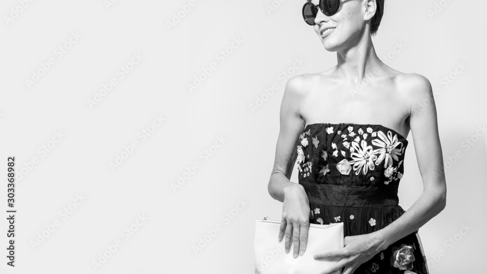 Fototapeta  portrait of stylish brunette woman in black sexy dress, holding hand bag and wearing sunglasses