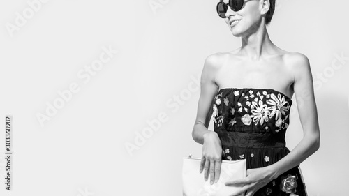 Fotografía  portrait of stylish brunette woman in black sexy dress, holding hand bag and we