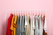 Leinwanddruck Bild - fashionable clothes on hangers on a wardrobe rack on a colored background.