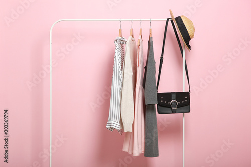 Pinturas sobre lienzo  fashionable clothes on hangers on a wardrobe rack on a colored background