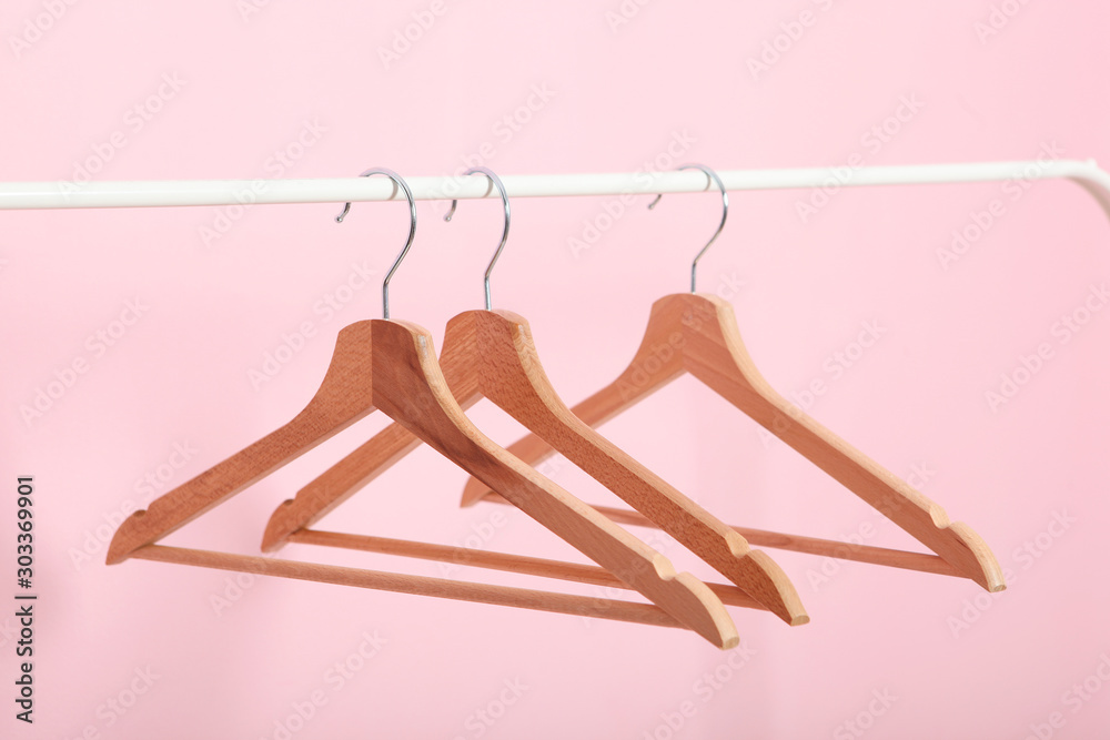 Fototapety, obrazy: empty clothes hangers on a wardrobe rack on a colored background.