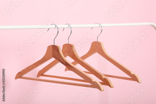 Fotografiet  empty clothes hangers on a wardrobe rack on a colored background.