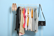 Fashionable Clothes On Hangers On A Wardrobe Rack On A Colored Background.