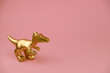 golden dinosaur statuette on pastel pink background with copy space trendy minimal art card