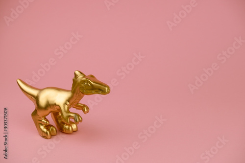 Obraz golden dinosaur statuette on pastel pink background with copy space trendy minimal art card - fototapety do salonu