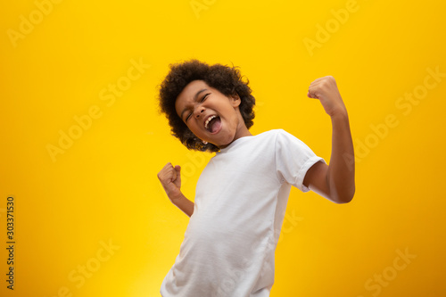 Obraz African American boy with black power hair on yellow background. Smiling black kid with a black power hair. Black boy with a black power hair. African descent. - fototapety do salonu