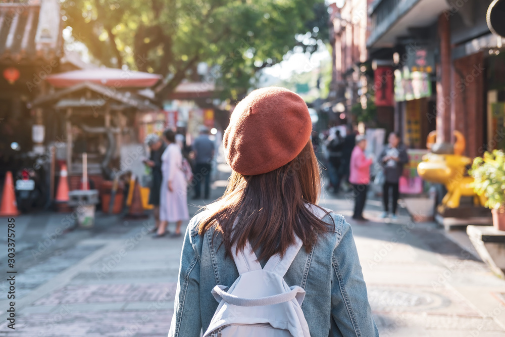 Fototapeta Young woman traveler walking in the shopping street, Travel lifestyle concept
