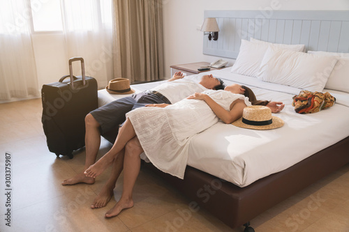 Young couple traveler with luggage sleeping on the bed in hotel room