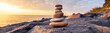 Leinwanddruck Bild - Stones pyramid on the seashore at sunset
