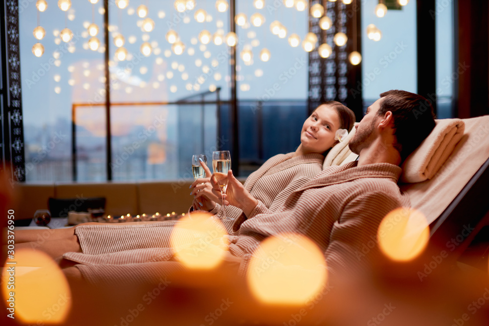 Fototapeta Young caucasian couple take care of body together lying in spa salon and drinking champagne, wearing bathrobe