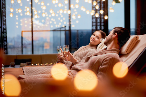 Obraz Young caucasian couple take care of body together lying in spa salon and drinking champagne, wearing bathrobe - fototapety do salonu