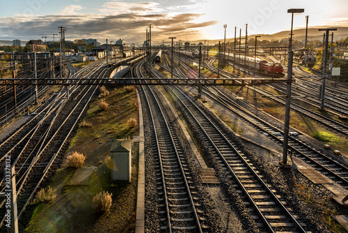 Modern European railway station at sunrise with rail tracks and trains