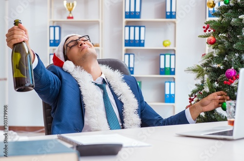 Vászonkép Businessman celebrating christmas holiday in the office