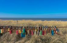 Love Locks, Hanging On A Rusty Fence At The Seaside Of North Holland. Outlook In Egmond Aan Zee With A Romantic Spot For Couples In Love, That Seal Their Relationship With This Symbol.