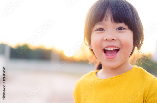 Slika na platnu Happy Little asian girl child showing front teeth with big smile and laughing: Healthy happy funny smiling face young adorable lovely female kid