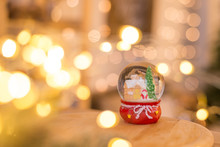 Christmas Decoration, Snow Dome, Globe With Table Decoration, Santaclaus On Sleigh With Child In Winter Scene, Christmas Tree With Lights In Background, Selective Focus