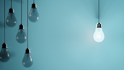 Hanging light bulbs on blue background with one illuminated and space for text