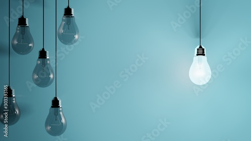 Obraz Hanging light bulbs on blue background with one illuminated and space for text - fototapety do salonu