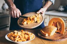 Man Cuts Pumpkin In The Kitchen