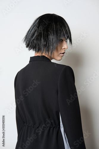 Fashion model in short black wig posing in profile Wall mural