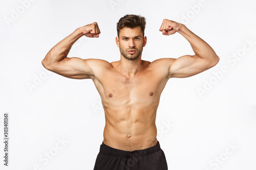 Sport, gym and strength concept. Sexy good-looking muscular young man in perfect shape, standing with naked torso, raising hands proudly showing strong big muscles, brag biceps, white background